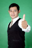 Asian young man thumbs-up. Against green background Royalty Free Stock Images