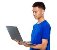 Asian young man use notebook computer Stock Photos