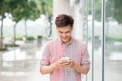 Asian young man using smart phone outdoor Stock Photography