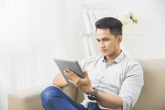 Asian young man using tablet pc at home Royalty Free Stock Photos
