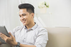 Asian young man using tablet pc at home Royalty Free Stock Image