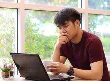 Free Asian Young Man Working In Coffee Shop Drinking Coffee , Looking At His Computer Laptop Stock Image - 160419231