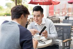 Asian young men enjoying watching on mobile phone together in ca. Fe with coffee on the table stock photos