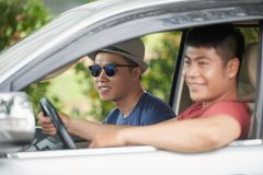 Traveling friends. Asian young men in hat and sunglasses traveling by car with friend Royalty Free Stock Images