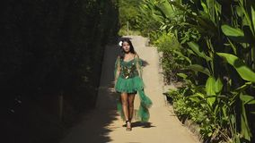 An asian model in a green dress goes on the road in the tropical garden. An asian young model in a green dress walking on the road among the green tropical stock video