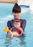 Asian young mother and cute eight month baby enjoy swimming pool Royalty Free Stock Photography