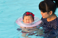 Asian young mother and cute eight month baby in swimming pool. Stock Images