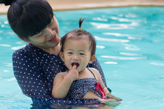 Asian young mother and cute one year baby playing swimming pool. Asian young mother and cute one year baby playing swimming pool, Active healthy family playing Stock Photo