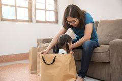 Asian young mother with little kid girl in shopping bag. Birthday concept Royalty Free Stock Image