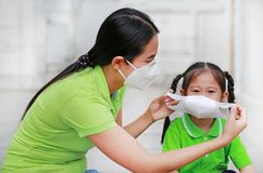 Asian young mother wearing protective mask for her daughter while outside to against PM 2.5 air pollution in Bangkok city. royalty free stock photo
