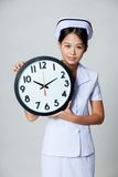Asian young nurse with a clock Stock Photography