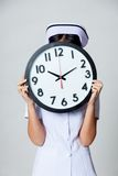 Asian young nurse close her face with a clock Stock Image