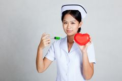 Asian young nurse hold syringe and red heart Royalty Free Stock Photo