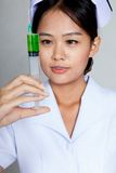 Asian young nurse look at syringe Royalty Free Stock Image