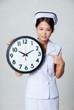 Asian young nurse point to a clock Stock Photography