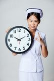 Asian young nurse show OK with a clock Stock Photography