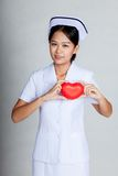 Asian young nurse show red heart on her chest Royalty Free Stock Images
