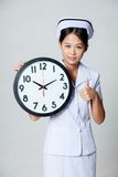 Asian young nurse show thumbs up with a clock Royalty Free Stock Photo