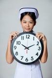 Asian young nurse smile with a clock Royalty Free Stock Photos