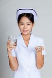 Asian young nurse smile with glass of water and pills Stock Photos