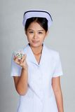 Asian young nurse smile with some pills Royalty Free Stock Photo
