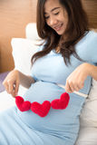 Asian young pregnant woman put heart shape accessories in her tu Stock Image