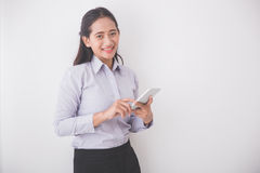 Asian Young secretary smiling while holding a cellphone. White b Royalty Free Stock Photography