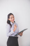 Asian Young secretary smiling while holding a clipboard. white b Stock Photos