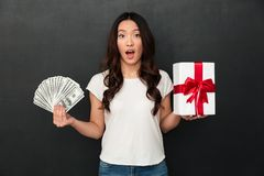 Asian young shocked woman holding money and gift box Stock Image