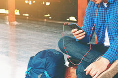 Asian young smart man hand holding mobile phone with linten music at train station. stock photos