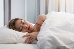 Asian young smiling pretty lady lies in bed indoors. Eyes closed royalty free stock photo