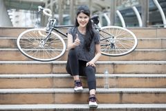 Asian young sport woman in sportswear sitting on the stairs with bicycle and showing thumbs up . girl taking a rest and relaxing. On street in urban city royalty free stock photos