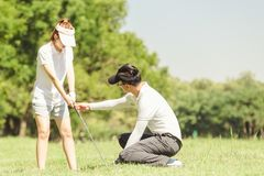 Golf Couple. Asian young sportive couple playing golf on a golf course, they walking talking happily royalty free stock image