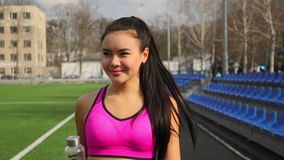Asian young sporty girl with bottle of water in hands is walking on stadium after training. Portrait of asian young sporty girl with bottle of water in hands is stock footage