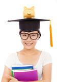 Asian young student holding book with piggy bank Royalty Free Stock Photos