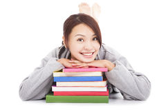 Asian young  student lying on stacked books Royalty Free Stock Photo