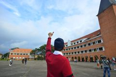 Young student at an old college. Asian young student standing with the victory hand at an old college in Dalat, Vietnam stock photos