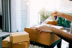 Asian young teenager owener of small business packing product in boxes preparing it for delivery stock image