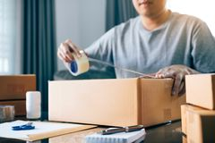 Asian young teenager owener of small business packing product in boxes preparing it for delivery stock images