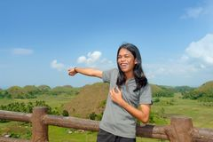 Asian young tourist showing landmark. Asian young teenager tourist showing the Bohol Chocolate Hills, a famous tourism landmark in the Philippines Stock Images
