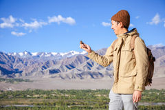 Asian young traveler looking at compass in Himalaya mountain view background in Leh, Ladakh, India Stock Photo
