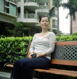 Asian young woman. Chinese young woman sitting at a bench. photo by film Royalty Free Stock Image