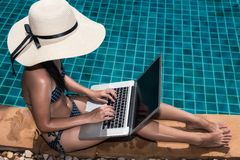 Asian Young woman in big hat relaxing on poolside with laptop co Stock Photography