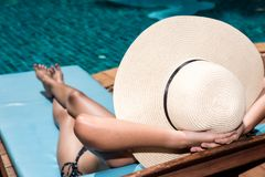 Asian young woman in big hat taking sunbath at swimming pool po. Olside blue water stock image