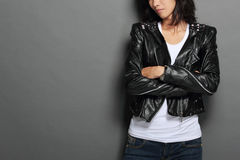 Asian young woman in black leather jacket on gray background Stock Images