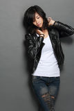 Asian young woman in black leather jacket on gray background Royalty Free Stock Image