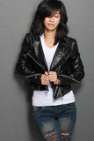 Asian young woman in black leather jacket on gray background Royalty Free Stock Photography