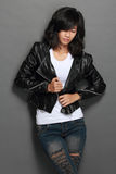 Asian young woman in black leather jacket on gray background Stock Photo