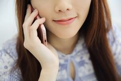 Asian young woman calling talking on phone callephohe in coffeeshop. In close up royalty free stock photography