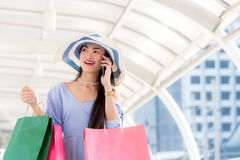 Asian young woman at the city with shopping bags talking on mobile phone. Stock Photography